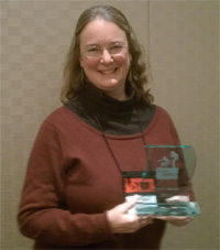 Author Kathleen Ernst holding LOVEY Award