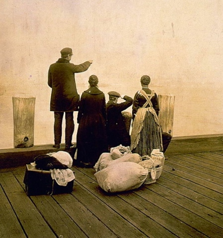 LC - [Four immigrants and their belongings, on a dock, looking out over the water; view from behind] Created / Published c1912 Oct. 30.