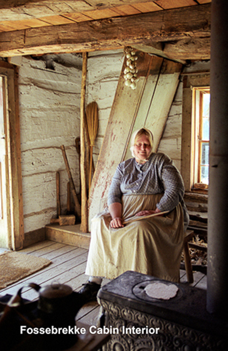 An interpreter cooks a pancake in the 1845 Fossebrekke (Norwegian) cabin.