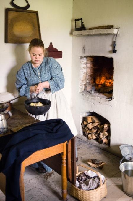 An interpreter prepares dinner in the 1860 Schulz kitchen.