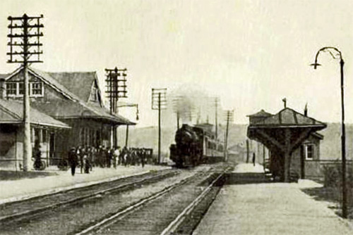 Vintage black and white photo of a C.M. & St. Paul railroad passenger train pulling into Hastings, MN circa 1920.