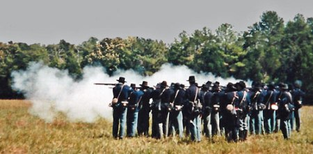 Color photo of Civil War Union Infantry reenactors conducting a musket firing drill at Old World Wisconsin in the 1980s courtesy of John Wedeward.